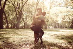 African American mother hugging her daughter in meadow. stock photo