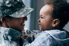 Mother in military uniform with son. African american mother in military uniform with her little son at home Royalty Free Stock Image