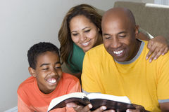 African American multicultural family reading The Bible. stock photo