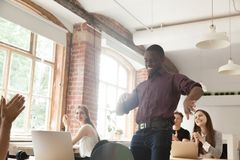 African american office employee dancing surrounded by coworkers Stock Images