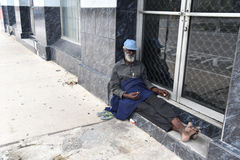 African American old homeless man. Port of spain, Trinidad and Tobago - November 28, 2015: old bearded man african American hobo or homeless sitting at building Stock Photography