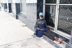 African American old homeless man. Port of spain, Trinidad and Tobago - November 28, 2015: old bearded man african American hobo or homeless sitting at building Stock Photo