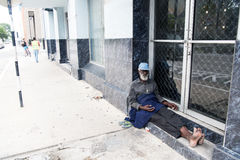 African American old homeless man. Port of spain, Trinidad and Tobago - November 28, 2015: old bearded man african American hobo or homeless sitting at building Royalty Free Stock Photo