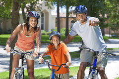African American Parents WIth Boy Son Riding Bike. A young African American family, women, men, father, mother & boy child riding bicycles in the summer Royalty Free Stock Images