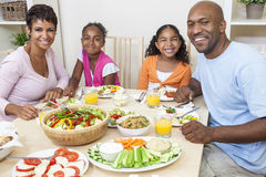 African American Parents Children Family Eating At Dining Table. An attractive happy African American, smiling family of mother, father, two daughters eating Stock Image