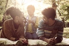 African American parents lying down in nature and talkin. Smiling African American parents lying down in nature and talking with little daughter royalty free stock image