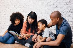 African American parents reading a fairy tale fable story. For kids at home. Happy family sitting on the floor indoors stock images