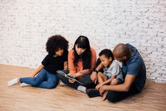 African American parents reading a fairy tale fable story for kids at home. Happy family sitting on the floor indoors. African American parents reading a fairy stock images