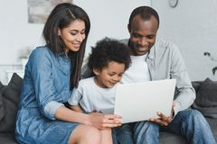 african american parents and son holding laptop and sitting on sofa stock images