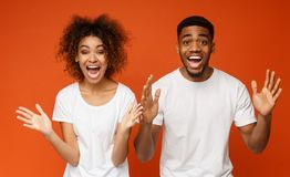 African-american partners rejoice success, clench fists and exclaim. Unbelievable! Surprised african-american men and women raising their hands in happy stock photo