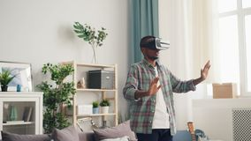 African American person is concentrated on interesting activity in virtual reality glasses moving hands standing in. Light apartment alone. House, modern stock video