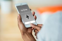 Free African American Person Sending A Ethereum Eth Crypto Transaction Using Mobile Phone Wallet - Black People Stock Photography - 122616692