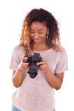 African American photographer reviewing pictures on her dslr cam Royalty Free Stock Image