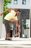 An African American picking up his skateboard Stock Photography