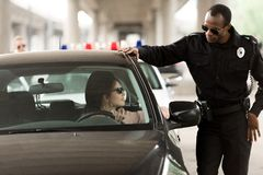 African american policeman talking to young woman sitting. In car stock photos
