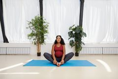 African American pregnant woman sitting at yoga studio royalty free stock photo