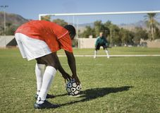 African American Preparing For A Penalty. Mature African American preparing for a penalty shot with goalkeeper in the background Stock Image