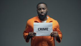 African-american prisoner holding Crime sign, looking to camera, awareness. Stock footage stock video