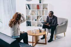African american psychiatrist sitting in armchair and talking to. Female patient Royalty Free Stock Photos