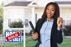 African American Real Estate Agent. Holding keys in front of sold house Stock Photo