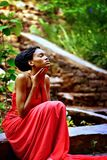 African-American retro model in the park. African American girl in a red dress, with dreadlocks sitting on a background of green plants on the rocks in the Park Royalty Free Stock Photos