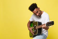 Young handsome African American retro styled guitarist playing acoustic guitar isolated on yellow gold background. African american retro styled guitarist stock photo