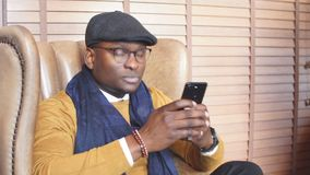 African american sales manager male waiting for his client in restaurant lounge. Sitting in armchair, spending time browsing internet on smartphone stock video