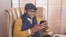 African american sales manager male waiting for his client in restaurant lounge. Sitting in armchair, spending time browsing internet on smartphone stock video footage