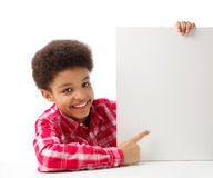African American school boy pointing at white blank. African American school boy, teenager smiling and ponting at empty white blank board, education and school Stock Photos