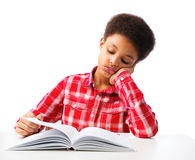 African American school boy reading book without interest. Bored African American school boy reading book without interest, education and school concept. Over Royalty Free Stock Image