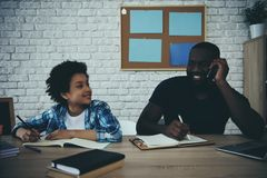 African American schoolboy doing homework. When father businessman working close by. Child education concept. Fatherhood royalty free stock photography