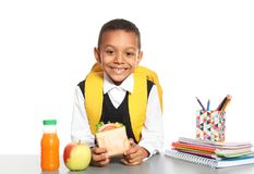 African-American schoolboy with healthy food. And backpack sitting at table on white background stock image