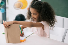 African american schoolgirl holding textbook and writing exercise at lesson Royalty Free Stock Images