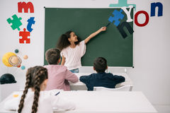 African american schoolgirl pointing at chalkboard while classmates studying at desks. Smiling african american schoolgirl pointing at chalkboard while royalty free stock image