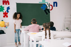 African american schoolgirl standing near chalkboard and looking at classmates sitting at desks Royalty Free Stock Photos
