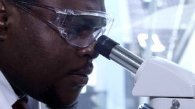 African-american scientist working in lab. Male doctor making microbiology research. Biotechnology, chemistry