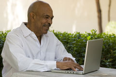 African American senior citizen working on laptop computer. African American senior citizen with laptop computer stock photo