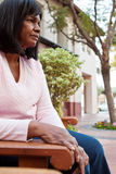 African American senior woman sitting on a bench. Stock Photography