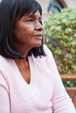 African American senior woman sitting on a bench. Stock Images