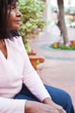 African American senior woman sitting on a bench. Stock Photos