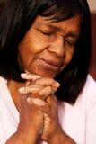 African American senior woman sitting on a bench praying. Stock Photo