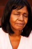 African American senior woman sitting on a bench praying. Stock Photos