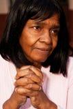 African American senior woman sitting on a bench praying. Royalty Free Stock Photos