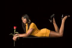 African-American  sexy girl with rose. Glamorous portrait of young beautiful woman holding rose flower Royalty Free Stock Photos