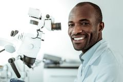African American short-haired beaming doctor openly smiling. Ordinary workday. African American short-haired beaming doctor openly smiling and showing his ideal royalty free stock images