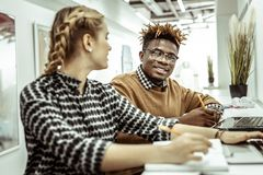 African American short-haired man pleasantly looking on female workmate. Girl writing down. African American short-haired men pleasantly looking on female stock images