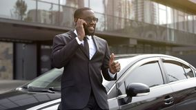African American showing thumbs-up speaking on phone, manager concluded bargain. Stock photo royalty free stock photos