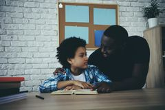 African American single father, along with son. Do homework at home. Child education concept royalty free stock images