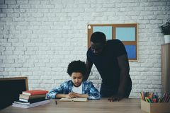 African American single father, along with son. Do homework at home. Child education concept stock image