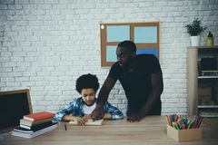 African American single father, along with son. Do homework at home. Child education concept stock photography
